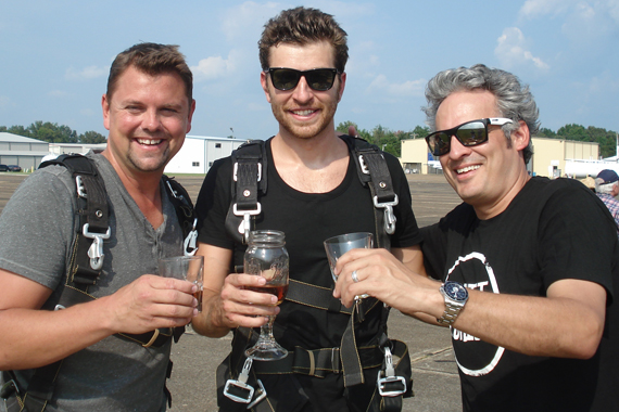 "Atlantic/WMN recording artist Brett Eldredge recently made good on his promise to skydive if his single ""Don't Ya"" made it to the top of the charts. Pictured (L-R): Storme Warren (SiriusXM), Eldredge, and Byron Kennedy (KNCI)"