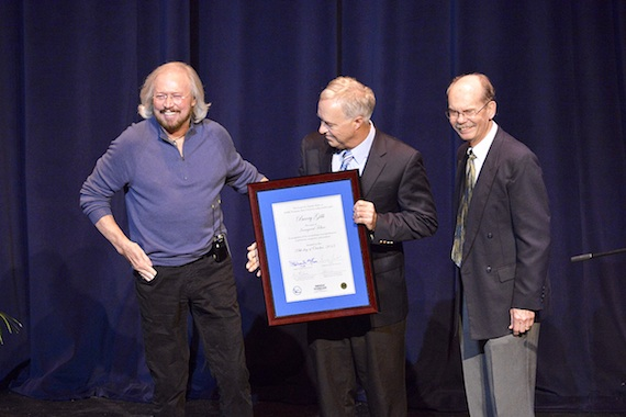 Singer-songwriter-producer Barry Gibb, left, laughs at an audience member's comment Monday night at MTSU during his recognition as the inaugural fellow of The Center for Popular Music in the university's College of Mass Communication. Presenting Gibb with documentation of his honor inside Tucker Theatre are mass comm Dean Ken Paulson, center, and Dr. Dale Cockrell, director of the center. (MTSU photo by Andy Heidt)