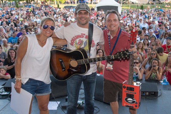 """BMI singer/songwriter Rhett Akins performs on the BMI Tailgate stage at CMA Fest. Akins has written a slew of country hits, including """"Hey Girl,"""" """"Parking Lot Party"""" and """"Young & Crazy."""" BMI's Jody Williams and Leslie Roberts present Rhett Akins with a custom Bohemian Guitar in celebration of the multiple Million Air awards he received that night, celebrating more than 25 titles with millions of spins."""