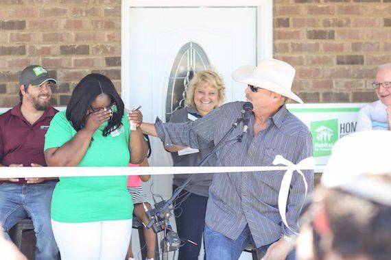 Alan Jackson hands the keys to new Rutherford County Area Habitat homeowner Keosha Hendricks and her daughter Akori' Yahah