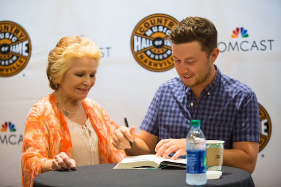 Scotty McCreery autographs a copy of his newbook Go Big or Go Home: The Journey Toward the Dream for a fan at theCountry Music Hall of Fame and Museum