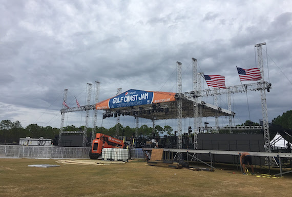 Crew works hard to strike the stage as winds begin to blow.
